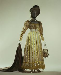 """Day Dress: ca. 1822, English, silk organdy with silk satin stripe. """"This style was sometimes found in the period of transition between the high-waist Empire style dresses of the early 19th century and the popular styles of the following period. The waistline approaches the natural waist position, while flounces and padding at the bottom of the skirt add weight to the thin and soft silk dress to create a beautiful skirt line. In the 1830s skirts came to have perfect bell shapes."""""""