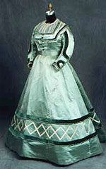 1860s gown with evening and day bodice of aqua silk satin trimmed with green velvet, ivory satin, and white beads.