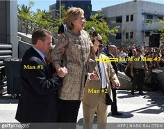 You saw this recent pic of Hillary being helped up the stairs by two men: Now, Kristinn Taylor of Gateway Pundit has discovered another photo of Hillary being held by a man to keep her from falling…