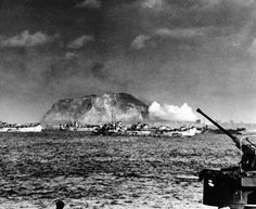 80-G-304823: Battle for Iwo Jima, February-March 1945. Heavy Naval units continue to bombard the rugged craters of Mt. Suribachi, February 19, 1945. U.S. Navy Photograph now in the collections of the National Archives.