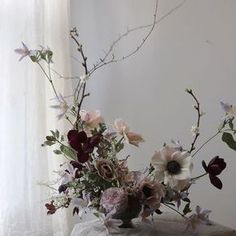 gorgeous centerpiece with soft rose and lilac colors and also some deep red accents and willow catkins for a garden inspired bouquet