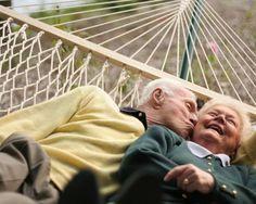 Señor besando a su esposa en una hamaca.