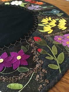 """Wool appliqué with crazy quilt stitching. Hand stitched by MaryAnnThom. Adapted from """"Flower Garden Crazy Tablemat""""by Primitive Gatherings."""