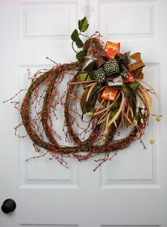 "A grapevine pumpkin shape with orange gypsum. Tied with a six patterned Terri Bow and grassy accents. Measures 27"" H X 27""W."