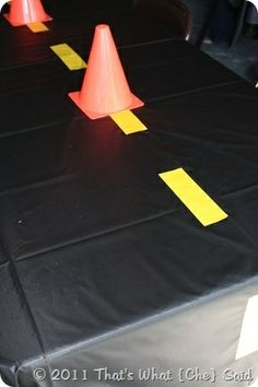 Black table cloth with yellow or white tape in the middle to make the road. then use table centerpieces as the cones to st on top