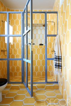 The walls and floor of a bathroom are lined in Popham Design's Hex Long Shadow.