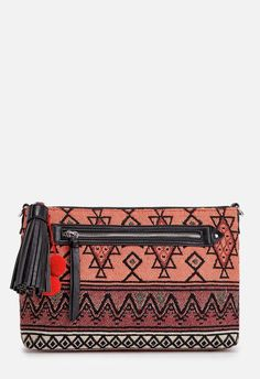 Add a vibrant touch to your look with this printed fabric clutch featuring a zip front compartment and a tassel zip top closure....