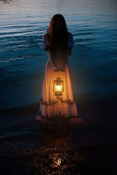 "This picture is sort of creepy, but it could be cool. ""There! A girl, standing in the water, held a lantern. She was far enough from the shore that no one would notice him. He swam up to her and stared. She stared back. 'So,' she said, 'Are you the mer-friend I found?' He nodded."""