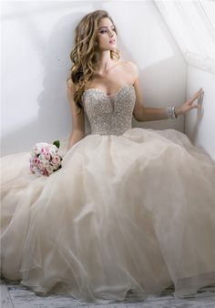 Angelette - Maggie Sottero Decadent crystal bodice complete with demure illusion center neckline and romantic Chic Organza skirt. Finished with zipper over inner corset and crystal button closure. Includes detachable center front motif.