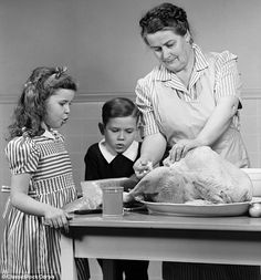 Stuffed! A girl watches as her mother gets the turkey ready for Thanksgiving dinner