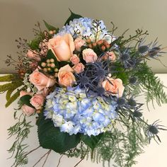 Blue and Peach themed clutch bouquet featuring hydrangeas, roses, spray roses, thistle, hypericum berries, millet and various greenery. #coastalbouquet #hydrangea #thistleandroses #blueandpeach