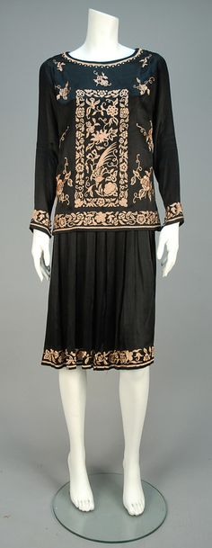 EMBROIDERED DAY DRESS, 1920s. 2-piece black silk having tunic embroidered in a pale pink Orientalist floral with birds, long sleeve with five self buttons at cuff, worn over a sleeveless dress with pleated skirt embroidered at hem. - whitakerauction
