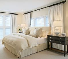 A very common problem - the only place for the bed is in front of the window.  These drapes are strategically placed to give the illusion the placement was purposeful, and it works beautifully.