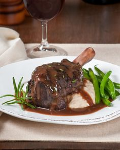 Crockpot Lamb Shanks Braised in Red Wine & Herbs served with roasted garlid white bean puree