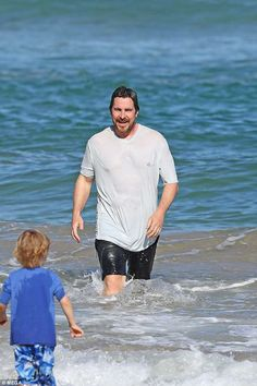 The actor recently dipped into the crystal blue ocean in Hawaii wearing a white T-shirt during some well-deserved rest and relaxation with his family. Hot Dads, Rest And Relaxation, Christian Bale, Hawaii Vacation, Surfs, Chris Hemsworth, Trunks, Actors, Swim Wear