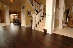 Love it all: dark wood floors, crown molding, staircase, wood detail on pillars, window at top of closet door, etc.