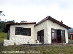Parte frontal casa diseñada en desnivel, puertas ventanas corredizas, amplios ventanales.