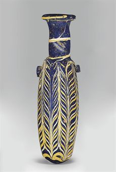 AN EASTERN MEDITERRANEAN CORE-FORMED GLASS ALABASTRON  CIRCA MID 2ND-EARLY 1ST CENTURY B.C.  Cobalt blue in color, the cylindrical body with a rounded bottom, rounded shoulders, cylindrical neck and wide disk rim, with applied white and yellow marvered threads attached at the rim and wound spirally along the length of the body and tooled into a feather pattern, an applied yellow thread at the edge of the rim, twin dark blue lugs on the shoulders  5½ in. (14 cm.) high