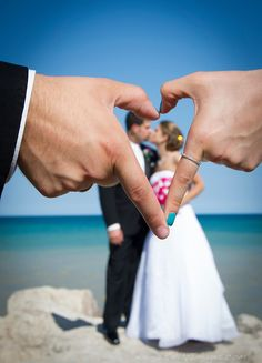 Wedding photo with the maid of honor and best man's hands forming a heart around the bride and groom.
