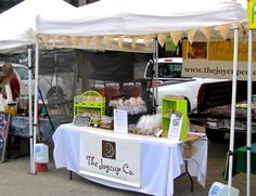 #FarmersMarket #vendorbooth ideas. A table banner, rustic tent banner and runner and painted thrift store rattan stands.