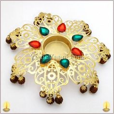 Brass diya, Rangoli diya, Diwali lamp, Vedicvaani.com, Religious oil lamps, wax diya, flashy rudraksha diyas online from India.  Desinger Rudraksh Diya, Designer Diya set in the center of a multicolored and well decorated hanging Java Rudraksh studded with colored gems. It's a tradition to light a lamp first before starting any auspicious events or rituals.Light symbolizes the absence of darkness,grief & unhappiness.Almighty's divine grace
