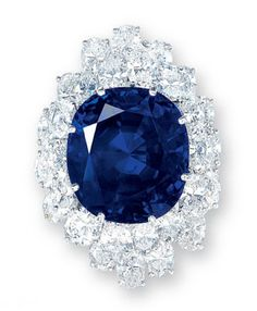 A SAPPHIRE AND DIAMOND RING. Set with a cushion-shaped sapphire, within a two-tiered oval-shaped diamond lozenge surround, mounted in platinum.
