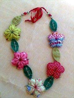 Maxi colar em flores de tecido, com folhas em feltro e detalhes de miçangas e fitas de cetim.