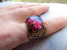 Dragons Breath Opal Ring Mexican Fire Opal Ring Opal Ring Fire Opal Ring Gothic Ring Art Deco Ring Art Nouveau Ring Filigree Ring- Spark  I used a stunning fiery red dragons breath opal that has complex colors of a fiery warmth of ruby red with shifting colors of cool purple and blue flashes in the bright light. The band is brass filigree with swirls and flowers on the side of the band and it is adjustable. Dragons breath opals are in limited supply since they are vintage jewels. There is…