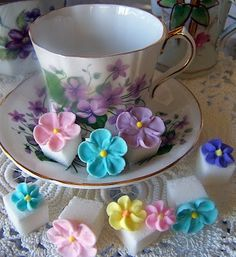 """Royal frosting flowers """"glued"""" to sugar cubes -- very pretty!!!  Drop one in your tea and watch the flower float to the top as the sugar cube melts!  :)"""