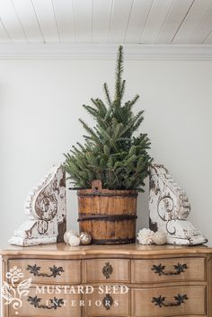 Miniature tree in an antique water bucket, ornaments, pom-poms, and a pair of antique corbels