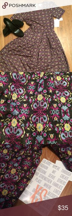 Lularoe Amelia nwt A beautiful pattern reminiscent of butterflies or flowers makes this dress perfect for any occasion. Magenta, sky blue, yellow, on a speckled black background LuLaRoe Dresses