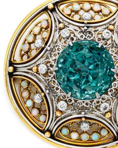 Gold, Platinum, Tourmaline, Opal and Diamond Brooch, Tiffany & Co., Designed by Louis Comfort Tiffany with Meta Overbeck:The openwork circular design centering a round tourmaline, accented by round diamonds weighing approximately .30 carat, bordered by white opals, signed Tiffany & Co., scratch number 248, one opal missing; circa 1910.Via Sotheby's