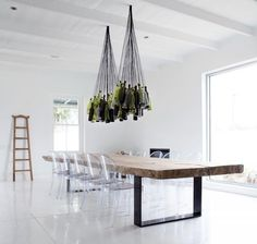 diy wine bottle chandelier, reclaimed wood table with metal strap legs and ghost chairs. minimalist design all white room makes the furniture the star Wine Bottle Chandelier, Diy Chandelier, Bottle Lamps, Pendant Lamps, Chandelier Creative, Pendant Lights, Pendants, Lampe Salon Design, Design Transparent