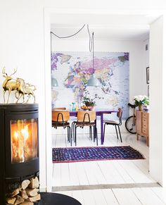 You've got to love a bold and brazen design choice like plastering a world map on your entire wall and then putting a bright purple dining table right in front! This dining room is every bit playful and lively. The bright and colorful world map wall mural and retro wooden chairs give the room a schoolhouse vibe, and the mid-century …