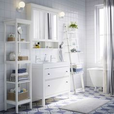 A white bathroom with HEMNES washstand, shelf, and mirror cabinet in white plus a blue shower curtain and blue and white towels.