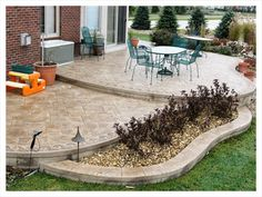 Here's a brown tinted two tiered stamped concrete patio with a built in flower bed.