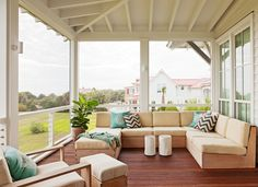 A screened-in porch off of the kitchen. Just off the kitchen, the top floor screened porch is a favorite area from which to look out at the ocean. A sectional sofa suited for the outdoors offers plenty of comfortable lounging or entertaining friends. This porch also features exposed rafters and steel cable railing.