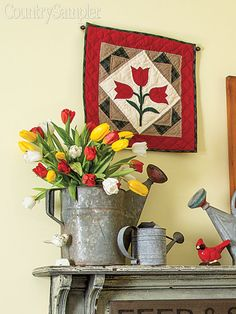 Fill an old galvanized watering can with bright and beautiful tulips to bring out the graphics of wall decor hung nearby.