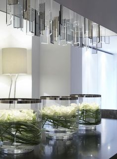 white roses in glass tank vases with wrapped leaves - Fiona Barratt Interiors - nice idea for beside the basin