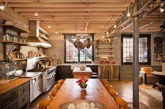 cuisine industrielle avec un plafond en bois à la française, des armoires en bois, des appareils électroménagers en inox et des murs en briques blanches