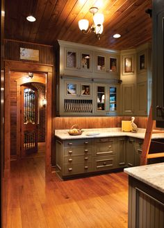 Upscale butlers pantry features the Beaded Deephaven door style finished in a custom Signature paint with Van Dyke Brown Highlight, distressing and wearing on maple.   Designed by: Nor-Son, Inc.  Photography by: Scott Admundson