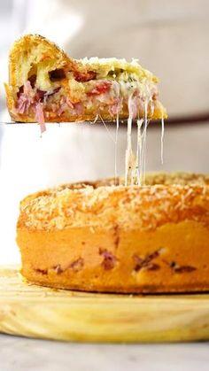 Receita com instruções em vídeo: Quem resiste a uma fácil e deliciosa torta pão de queijo recheada? Ingredientes: 3 xícaras de polvilho azedo, 3 ovos, 1 xícara de queijo minas ralado, ½ xícara de óleo, 1 xícara de leite morno, Pitada de sal, 1 colher de chá de fermento químico, 200g de presunto picado, 100g de bacon picado, 100g de queijo muçarela ralado, 1 xícara de tomatinhos cereja cortados ao meio , 1 colher de chá de orégano, 1 xícara de queijo parmesão ralado