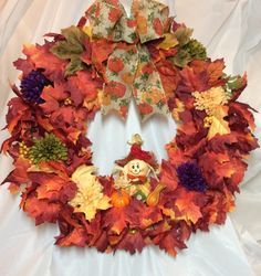 "Fall scarecrow wreath. Maple leaves and fall mums on 18"" grapevine form, stuffed scarecrow. Pumpkin print bow. Fall colors. Chenille hanger. by KhQualityCreations on Etsy"