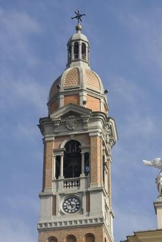 Campanile della chiesa di San Giovanni Battista a Latisana (UD). L'attuale campanile alto 63 metri fu ricostruito nel 1920: ha tipologia a torre isolata, fusto a pianta quadrata con feritoie e quadrante di orologio che parte da un basamento a contrafforti, cella campanaria con serliane sormontate da cornicione con timpano, tiburio ottagonale con cupola a otto spicchi, terminante in lanterna cupolata. [SIRPAC - Scheda 8237]