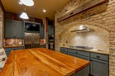 This quant country kitchen features a beautiful neutral brick arched wall surrounding the stove area. A neutral marble tile backsplash adds a lovely polished contrast next to the brick and matte blue cabinets. A wooden kitchen island provides great work space, and a yellow ceiling brightens the room.