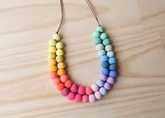 wo Strand Rainbow Necklace is a mini statement piece. It can be worn long or short as a bib necklace and can be simply tied with an overhand knot. Threaded onto brown cotton cord, this bright piece features a rainbow assortment of 48 hand rolled beads in 20 custom made colours. $ 55 AUS sydney Ena and Albert