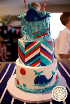 "Red, white, teal, and blue first birthday cake. Top layer ""waves"" smash cake. Hand cut whales and offset chevrons. With bunting.  All edible but straws."