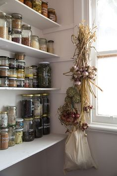 love this bulk pantry full of mismatched jars, drying garlic, and hanging onions.