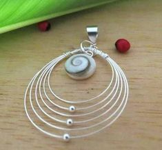 Slender wire forms a perfect round shape to border this Shiva shell pendant. The round 10 mm. of Shiva shell is classic, with a smooth white background and a simple brown swirl. The Shiva shell is secured within the smooth round open wired multiple hoops that frames it. A thick sterling silver bail completes this elegant Shiva shell open multiple hoops wire pendant.