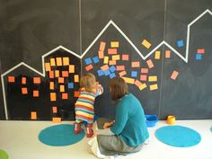 Tape & post-it cityscape on a wall. Great provocation for little ones.